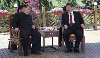 FILE - In this file photo taken between May 7 and 8, 2018, released by China's Xinhua News Agency, Chinese President Xi Jinping, right, speaks to North Korean leader Kim Jong Un in Dalian in northeastern China's Liaoning Province. As North Korea celebrates the 70th anniversary of its founding on Sunday, Sept. 9, 2018, the presence - or absence - of Xi could highlight just how much vitality has been restored to ties between Pyongyang and its most powerful backer after a prolonged chill. (Ju Peng/Xinhua via AP, File)