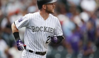 Colorado Rockies' Trevor Story follows the flight of his two-run home run off San Francisco Giants starting pitcher Madison Bumgarner in the first inning of a baseball game Monday, Sept. 3, 2018, in Denver. (AP Photo/David Zalubowski)
