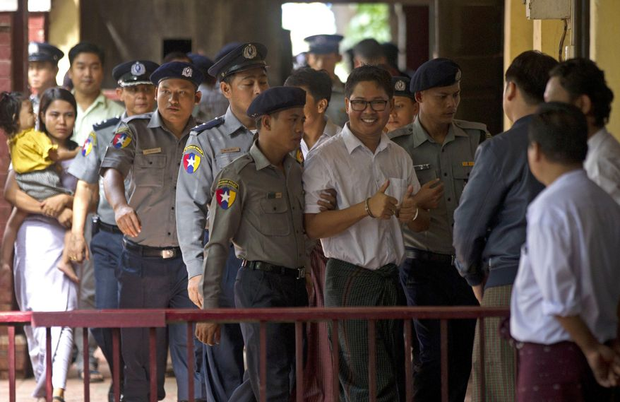 Reuters journalist Wa Lone, center, is escorted by polices upon arrival at the court Monday, Sept. 3, 2018, in Yangon, Myanmar. A Myanmar court sentenced two Reuters journalists, Wa Lone and Kyaw Soe Oo, to seven years in prison Monday for illegal possession of official documents, a ruling that comes as international criticism mounts over the military's alleged human rights abuses against Rohingya Muslims.  (AP Photo/Thein Zaw)