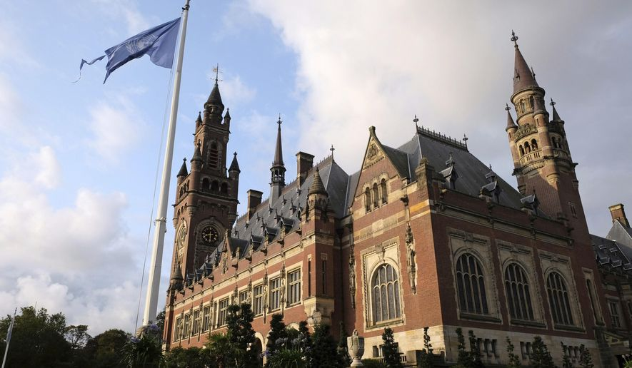 -FILE- In this Monday Aug. 27, 2018, image, the United Nations flag flutters in the wind next to the International Court of Justice in the Hague, the Netherlands. Judges at the United Nations' highest court are listening to arguments in a case focused on whether Britain illegally maintains sovereignty over the Chagos Islands in the Indian Ocean, including Diego Garcia, where the United States has a major military base. (AP Photo/Mike Corder)