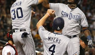 San Diego Padres Franmil Reyes gets a high fives from Eric Hosmer (30) and Wil Myers (4) after hitting a three-run home run against the Arizona Diamondbacks in the second inning during a baseball game, Monday, Sept. 3, 2018, in Phoenix. (AP Photo/Rick Scuteri)