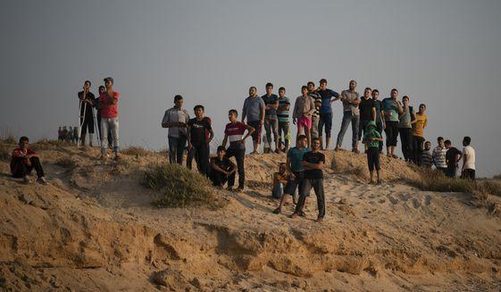 Palestinian protesters gather on the beach near the border with Israel in Beit Lahiya, northern Gaza Strip, Sunday, Sept. 2, 2018. (AP Photo/Felipe Dana)
