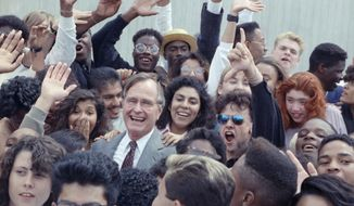 """FILE- In this May 21, 1990, file photo, U.S. President George H.W. Bush is surrounded by cheering students from the Independent Living Program in Los Angeles, as Bush prepared to leave Los Angeles International Airport. President Donald Trump may have ridiculed former President George H.W. Bush's """"thousand points of light"""" this summer but the concept is still going strong three decades later. (AP Photo/Marcy Nighswander, File)"""