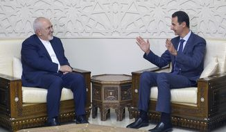 "In this photo released by the Syrian official news agency SANA, Syrian President Bashar Assad, right, speaks with Iranian Foreign Minister Mohammad Javad Zarif in Damascus, Syria, Monday, Sept 3, 2018. Zarif said at the start of a visit to Damascus on Monday that ""terrorists must be purged"" from Syria's Idlib and the entire northwestern province returned to government control. (SANA via AP)"