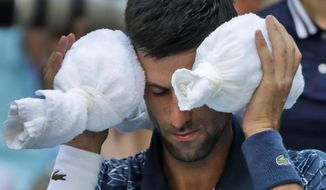 Novak Djokovic, of Serbia, puts an ice towel around his head during a changeover against Joao Sousa, of Portugal, during the fourth round of the U.S. Open tennis tournament, Monday, Sept. 3, 2018, in New York. (AP Photo/Carolyn Kaster)