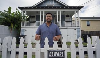 In this Aug. 28, 2018, photo, Alex Ramirez poses in front of one of his short-term rental properties that he refurbished from a blighted state, in Mid City New Orleans. New Orleans officials are looking at the benefits and headaches of the vacation rental industry that has proliferated with the growth of online sites such as Airbnb. They've put a halt, for now, on approving or renewing licenses for the short-term rental of whole houses in much of the city. Some rental property owners are crying foul, saying they are being unfairly punished while contributing to the city's vital tourism industry. (AP Photo/Gerald Herbert)