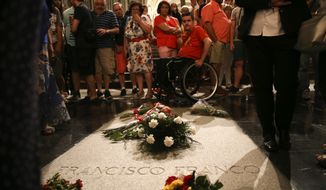 People stand around the tomb of former Spanish dictator Francisco Franco inside the basilica at the the Valley of the Fallen monument near El Escorial, outside Madrid, Friday, Aug. 24, 2018. Spain's center-left government has approved legal amendments that it says will ensure the remains of former dictator Gen. Francisco Franco can soon be dug up and removed from a controversial mausoleum. (AP Photo/Andrea Comas)