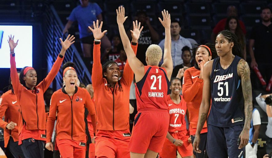 Washington Mystics center Krystal Thomas, second from right, forward Tianna Hawkins (21), forward Myisha Hines-Allen, fourth from right, and forward Aerial Powers, second from left, celebrate as Atlanta Dream forward Jessica Brelaat stands nearby, at the end of Game 5 in a WNBA basketball playoffs semifinal Tuesday, Sept. 4, 2018, in Atlanta. The Mystics won 86-8 to advance to the finals. (AP Photo/John Amis)