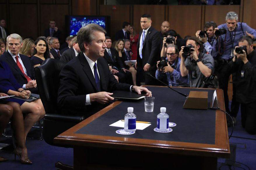 Supreme Court nominee Brett Kavanaugh, listens to Senate Judiciary Committee Chairman Sen. Chuck Grassley, R-Iowa, after giving his opening statement during the committee's nominations hearing on Capitol Hill in Washington, Tuesday, Sept. 4, 2018. Former Secretary of State Condoleezza Rice is seated back left. (AP Photo/Manuel Balce Ceneta)