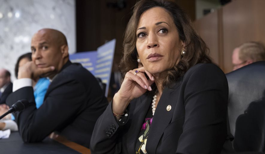 Sen. Kamala Harris, D-Calif., and Sen. Cory Booker, D-N.J., left, pause as protesters disrupt the confirmation hearing of President Donald Trump's Supreme Court nominee, Brett Kavanaugh, on Capitol Hill in Washington, Tuesday, Sept. 4, 2018. (AP Photo/J. Scott Applewhite)