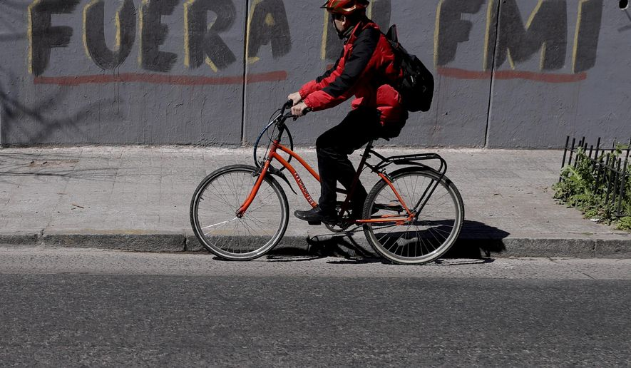 "A man rides his bicycle past the Spanish graffiti message: ""Get out IMF"" in Buenos Aires, Argentina, Tuesday, Sept. 4, 2018. In recent weeks, the currency crisis in Argentina has intensified, forcing the government to ask for an early release of a credit line from the International Monetary Fund. (AP Photo/Natacha Pisarenko)"