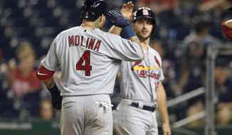 St. Louis Cardinals' Yadier Molina (4) celebrates his grand slam with Paul DeJong, back, during the ninth inning of a baseball game against the Washington Nationals, Tuesday, Sept. 4, 2018, in Washington. The Cardinals won 11-8. (AP Photo/Nick Wass)