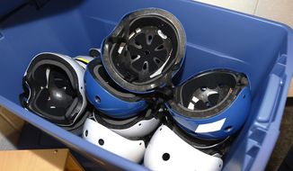 FILE - This Aug. 12, 2014 file photo shows safety helmets in a container in a pre-K classroom at an elementary school in Oklahoma. Comprehensive new children's concussion guidelines from the U.S. government released on Tuesday, Sept. 4, 2018, recommend against routine X-rays and blood tests for diagnosis and reassure parents that most kids' symptoms subside within one to three months. (AP Photo/Sue Ogrocki)