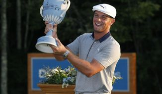 Bryson DeChambeau holds the trophy after winning the Dell Technologies Championship golf tournament at TPC Boston in Norton, Mass., Monday, Sept. 3, 2018. (AP Photo/Michael Dwyer)