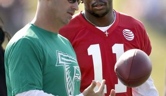 FILE - In this July 27, 2018, file photo, Atlanta Falcons offensive coordinator Steve Sarkisian, left, talks with wide receiver Julio Jones at an NFL football training camp practice in Flowery Branch, Ga.  It's been eight months since the Atlanta Falcons' season ended on fourth-and-goal at the 2-yard line in Philadelphia. Offensive coordinator Steve Sarkisian says he's moved on from his questionable play call, but there's a better way to change the narrative _ start fast and build a big lead Thursday night against the Eagles. (AP Photo/David Goldman, File)