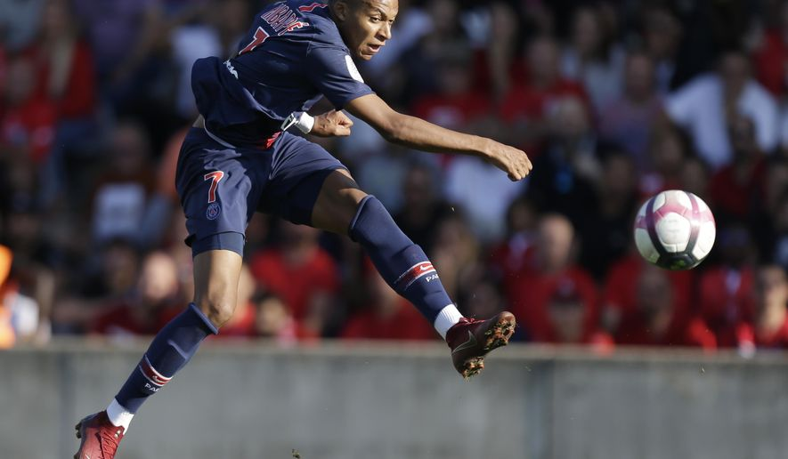 PSG's Kylian Mbappe kicks the ball during their League One soccer match between Nimes and Paris Saint-Germain at Jean-Bouin stadium in Nimes, southern France, Saturday Sept. 1, 2018. (AP Photo/Claude Paris)