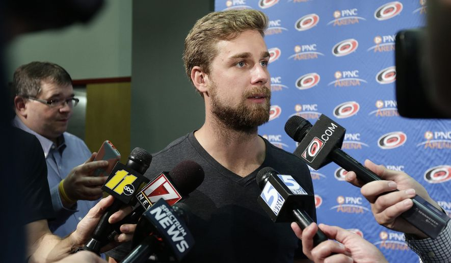 Carolina Hurricanes' Calvin de Haan takes questions from members of the media during the NHL hockey team's media day in Raleigh, N.C., Tuesday, Sept. 4, 2018. (AP Photo/Gerry Broome)