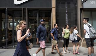 People pass a Nike store in New York, Tuesday, Sept. 4, 2018. An endorsement deal between Nike and Colin Kaepernick is prompting a flood of debate online as sports fans react to the apparel giant backing an athlete known mainly for starting a wave of protests among NFL players of police brutality, racial inequality and other social issues. (AP Photo/Mark Lennihan)