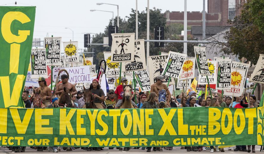 In this Aug. 6, 2017, file photo, demonstrators against the Keystone XL pipeline march in Lincoln, Neb. (AP Photo/Nati Harnik, file)