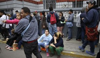 Venezuelans who recently moved to Peru wait outside the Venezuelan embassy to try to get on a list for a government-financed flight home, in Lima, Peru, Tuesday, Sept. 4, 2018. Some of the migrants said they prefer to return because they haven't found work or the working conditions were not what they expected in Peru. (AP Photo/Martin Mejia)