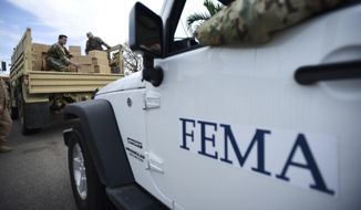 In this Oct. 5, 2017, file photo, Department of Homeland Security personnel deliver supplies to Santa Ana community residents in the aftermath of Hurricane Maria in Guayama, Puerto Rico. (AP Photo/Carlos Giusti, File) **FILE**