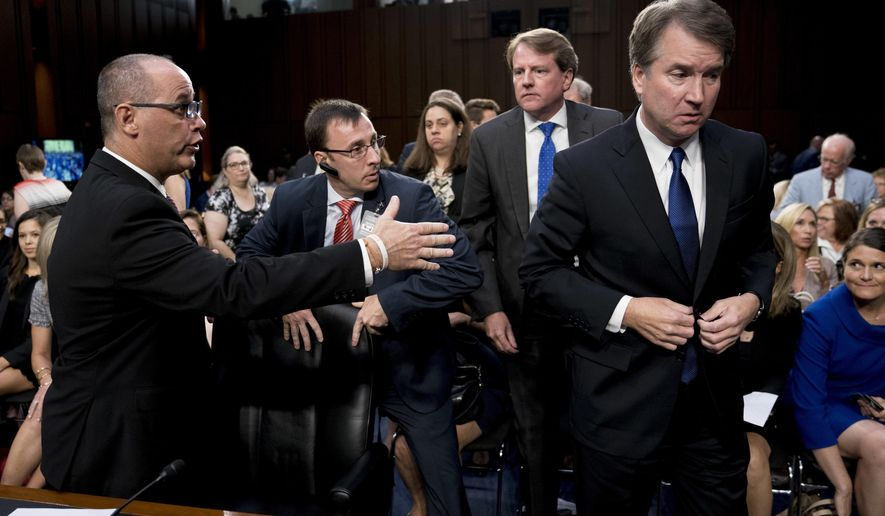 White House counsel Don McGahn, second from right, watches as Fred Guttenberg, the father of Jamie Guttenberg who was killed in the Stoneman Douglas High School shooting in Parkland, Fla., left, attempts to shake hands with President Donald Trump's Supreme Court nominee, Brett Kavanaugh, a federal appeals court judge, right, as he leaves for a lunch break while appearing before the Senate Judiciary Committee on Capitol Hill in Washington, Tuesday, Sept. 4, 2018, to begin his confirmation to replace retired Justice Anthony Kennedy. Kavanaugh did not shake his hand. (AP Photo/Andrew Harnik)