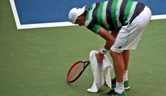 John Isner bends over during a match against Juan Martin del Potro, of Argentina, during the quarterfinals of the U.S. Open tennis tournament, Tuesday, Sept. 4, 2018, in New York. (AP Photo/Andres Kudacki)