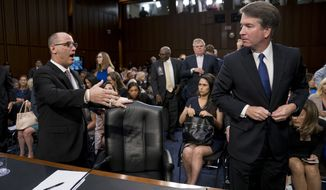 Fred Guttenberg, the father of Jamie Guttenberg who was killing in the Stoneman Douglas High School shooting in Parkland, Fla., left, attempts to shake hands with President Donald Trump's Supreme Court nominee, Brett Kavanaugh, a federal appeals court judge, right, as he leaves for a lunch break while appearing before the Senate Judiciary Committee on Capitol Hill in Washington, Tuesday, Sept. 4, 2018, to begin his confirmation to replace retired Justice Anthony Kennedy. Kavanaugh did not shake his hand. (AP Photo/Andrew Harnik)