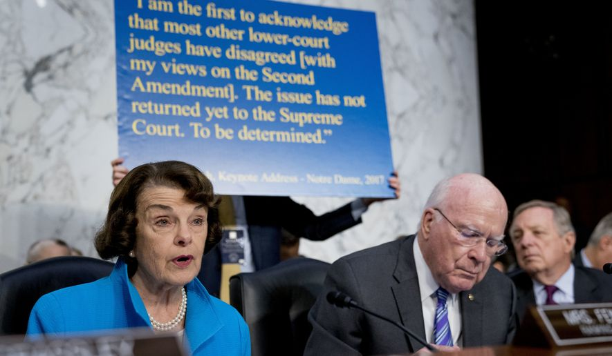 A poster depicting a 2017 quote on the Second Amendment by President Donald Trump's Supreme Court nominee, Brett Kavanaugh, a federal appeals court judge, is held up behind Sen. Dianne Feinstein, D-Calif., the ranking member on the Senate Judiciary Committee, left, as she questions Kavanaugh as he testifies before the Senate Judiciary Committee on Capitol Hill in Washington, Wednesday, Sept. 5, 2018, for the second day of his confirmation to replace retired Justice Anthony Kennedy. Also pictured is Sen. Patrick Leahy, D-Vt., second from right, and Sen. Dick Durbin, D-Ill., right. (AP Photo/Andrew Harnik)