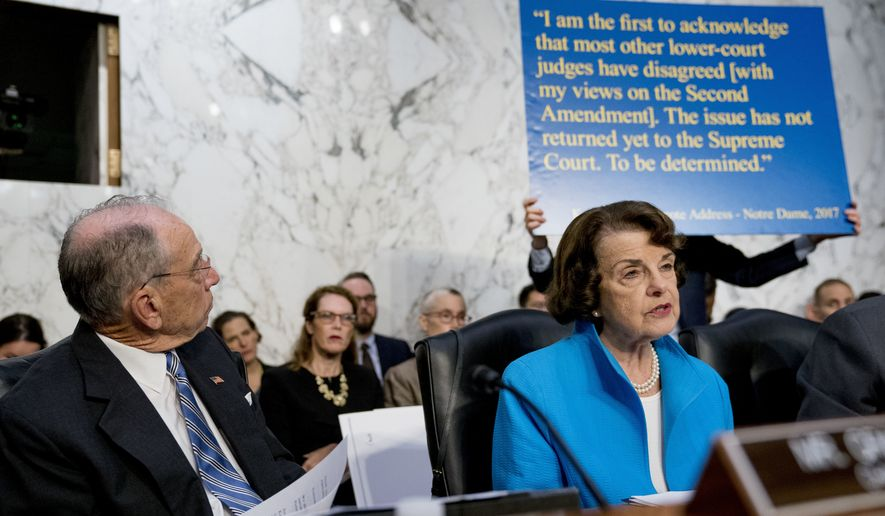 A poster depicting a 2017 quote on the Second Amendment by President Donald Trump's Supreme Court nominee, Brett Kavanaugh, a federal appeals court judge, is held up behind Sen. Dianne Feinstein, D-Calif., the ranking member on the Senate Judiciary Committee, right, as she questions Kavanaugh as he testifies before the Senate Judiciary Committee on Capitol Hill in Washington, Wednesday, Sept. 5, 2018, for the second day of his confirmation to replace retired Justice Anthony Kennedy. Also pictured is Senate Judiciary Committee Chairman Chuck Grassley, R-Iowa, left. (AP Photo/Andrew Harnik)