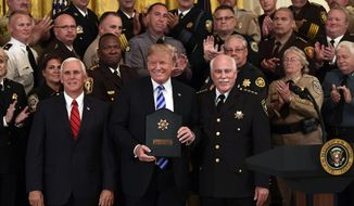 President Donald Trump, center, poses for a photos with Vice President Mike Pence, front left, and Bristol County, Mass., Sheriff Thomas Hodgson, front right, during an event with sheriffs in the East Room of the White House in Washington, Wednesday, Sept. 5, 2018. (AP Photo/Susan Walsh)