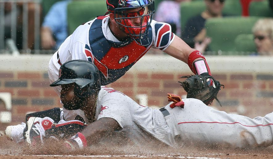 Boston Red Sox's Brandon Phillips slides home safely to score past Atlanta Braves catcher Tyler Flowers during the eighth inning of a baseball game on Wednesday, Sept 5, 2018, in Atlanta. (Curtis Compton/Atlanta Journal-Constitution via AP)