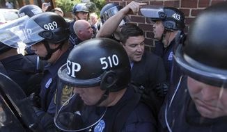 FILE - In this Aug. 13, 2017 file photo, Unite the Right rally organizer Jason Kessler, center rear, is escorted by police after his press conference was disrupted by protestors outside City Hall in Charlottesville, Va. Jeffrey Winder, a Virginia man convicted of assault against Kessler, the organizer of last summer's violent white nationalist rally, has been handed a $1 fine. (Andrew Shurtleff/The Daily Progress via AP, File)