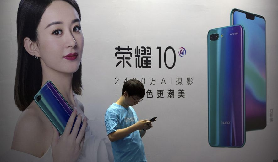 FILE - In this April 26, 2018, file photo, a staff member uses his smartphone in front of a billboard for Chinese cellphone maker Honor at the Global Mobile Internet Conference (GMIC) in Beijing. The head of China's patent and copyright agency is defending what he says are gains in fighting violations - once a chronic complaint by China's trading partners - in a new effort to defuse a tariff war with Washington. (AP Photo/Mark Schiefelbein, File)
