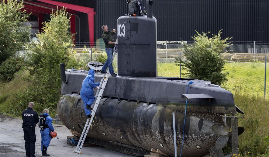 FILE - In this Sunday, Aug. 13, 2017 file photo, police technicians board Peter Madsen's submarine UC3 Nautilus on a pier in Copenhagen harbour, Denmark. Danish submarine inventor Peter Madsen, who was found guilty of the torture, sexual assault, murder and dismemberment of a Swedish reporter, appeared before an appeals court Wednesday Sept. 5, 2018, to fight against his life sentence. (Jacob Ehrbahn/Ritzau Foto, File via AP)