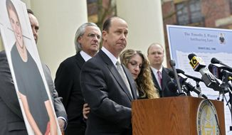 FILE - In this March 23, 2018, file photo, Jim Piazza speaks about the importance of passing anti-hazing legislation named after his son, Timothy Piazza, a Penn State University student who died after a night of hazing and drinking at a fraternity, as his wife Evelyn wraps her arm around him outside of the Centre County Courthouse in Bellefonte, Pa. Timothy Piazza's parents have settled with Beta Theta Pi's national organization. (Abby Drey/Centre Daily Times via AP, File)