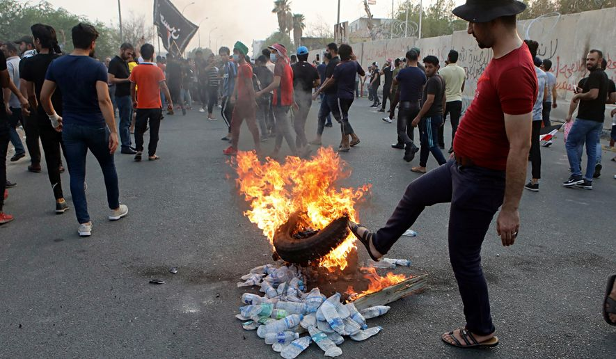 Protesters set a tire on fire in front of the provincial council building during protests demanding better public services and jobs, Tuesday, Sept. 4, 2018, in Basra, 340 miles (550 kilometers) southeast of Baghdad, Iraq. Iraqi security forces fired tear gas and live ammunition on hundreds of protesters. (AP Photo/Nabil al-Jurani)