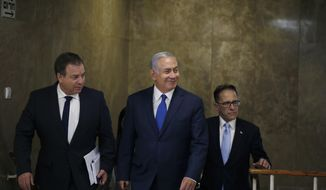Israeli Prime Minister Benjamin Netanyahu, center, arrives to the weekly cabinet meeting at the Prime Minister's office in Jerusalem on Wednesday, Sept. 5, 2018. (Ronen Zvulun/Pool Photo via AP)