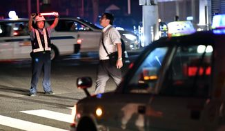 A police officer controls the traffic during a blackout following a strong earthquake in Sapporo, northern Japan early Thursday, Sept. 6, 2018.  A powerful earthquake struck the island of Hokkaido early Thursday. (Yu Nakajima/Kyodo News via AP)