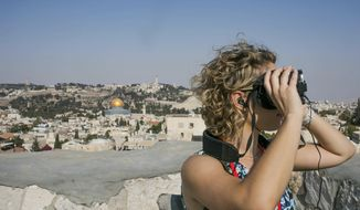 In this Monday, Sept. 3, 2018 photo, released by the Tower of David Museum, a visitor uses goggles on a new virtual reality tour that allows visitors to experience how archaeologists believe Jerusalem looked 2,000 years ago. The museum, which is housed in the Old City's ancient stronghold, plans to launch the high-tech guided tour in September ahead of the Jewish holiday of Sukkot. (Tomer Zmora/Tower of David Museum via AP)