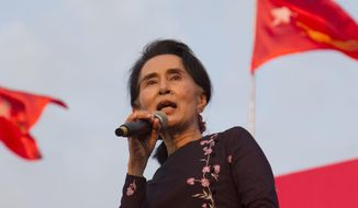 FILE - In this Nov. 1, 2015, file photo, Myanmar opposition leader Aung San Suu Kyi speaks during an election campaign rally of her National League for Democracy party for upcoming general election in Yangon, Myanmar. Myanmar's government looks as if it's under siege from an international community concerned about the condition of its nascent democracy, with widespread calls for a genocide tribunal to hold its military to account for brutal treatment of its Muslim Rohingya minority. (AP Photo/Khin Maung Win, File)