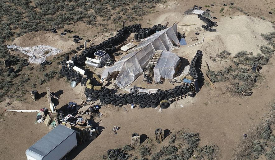 FILE - This Aug. 10, 2018, file photo shows a ramshackle compound in the desert area of Amalia, N.M. Five former residents of the compound in northern New Mexico where a 3-year-old boy's body was found last month are scheduled to appear in federal court on firearms-related charges. A hearing Tuesday, Sept. 4, 2018 focuses on allegations against  Jany Leveille of illegal possession of firearms and ammunition linked to her unlawful immigration status and conspiracy accusations against the four other defendants. (AP Photo/Brian Skoloff, File)