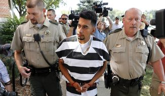 FILE - In this Aug. 22, 2018, file photo, Cristhian Bahena Rivera is escorted into the Poweshiek County Courthouse for his initial court appearance in Montezuma, Iowa. Rivera is charged with first-degree murder in the death of Iowa college student Mollie Tibbetts, who disappeared July 18 from Brooklyn, Iowa. The Mexican national was known by another name on the dairy farm where he worked for the last four years: John Budd. It was confirmed by three people with knowledge of his employment history, who spoke on condition of anonymity. (AP Photo/Charlie Neibergall, File)