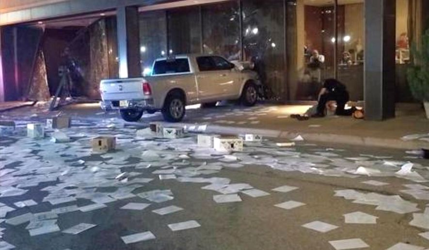 This photo from video by KDFW Fox 4 shows a man being detained at right after crashing his pickup truck into the side of the Fox affiliate television station building in downtown Dallas on Wednesday, Sept. 5, 2018. Despite the crash, nobody was hurt. (KDFW Fox 4 via AP)