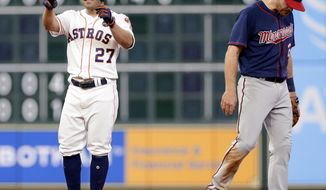 Houston Astros' Jose Altuve (27) reacts next to Minnesota Twins second baseman Logan Forsythe at second base after Altuve hit an RBI double, scoring George Springer, during the sixth inning of a baseball game Wednesday Sept. 5, 2018, in Houston. (AP Photo/Michael Wyke)