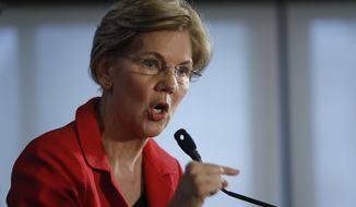 Sen. Elizabeth Warren, D-Mass., gestures while speaking at the National Press Club in Washington, Tuesday, Aug. 21, 2018. Warren wants a lifetime ban on members of Congress from getting hired as lobbyists after they leave public office. She also wants to prohibit lawmakers from owning or trading individual stocks while in office. (AP Photo/Pablo Martinez Monsivais)