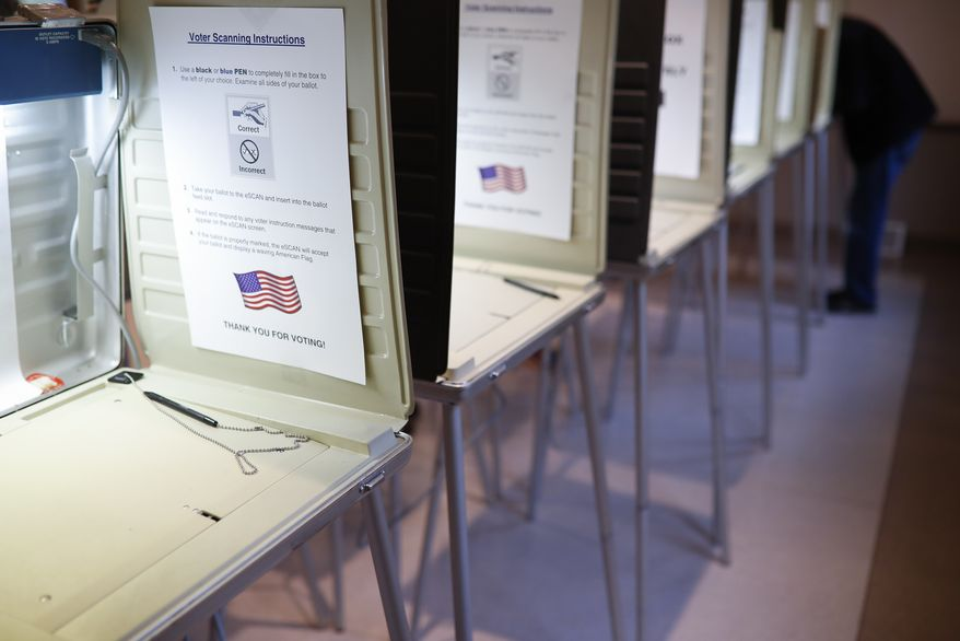 In this Nov. 8, 2016, file photo, a lone voter fills out a ballot alongside a row of empty booths at a polling station in the Terrace Park Community Building on Election Day in Cincinnati. (AP Photo/John Minchillo, File)