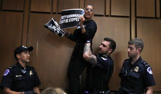A protester is lifted off of a chair by U.S. Capitol Police while standing on it and shouting during testimony by President Donald Trump's Supreme Court nominee Brett Kavanaugh on the third day of Kavanaugh's Senate Judiciary Committee confirmation hearing, Thursday, Sept. 6, 2018, on Capitol Hill in Washington, to replace retired Justice Anthony Kennedy. (AP Photo/Jacquelyn Martin)