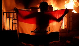 A man holds a national flag while protesters burn the municipal complex during protests demanding better public services and jobs in Basra, 340 miles (550 km) southeast of Baghdad, Iraq, Wednesday, Sept. 5, 2018. (AP Photo/Nabil al-Jurani)
