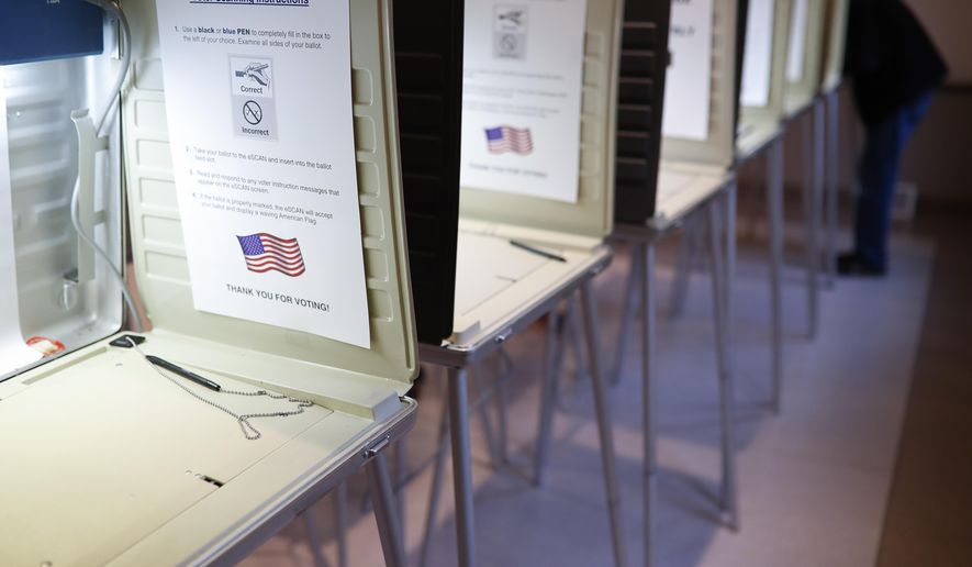 In this Nov. 8, 2016, file photo a lone voter fills out a ballot alongside a row of empty booths at a polling station in the Terrace Park Community Building on Election Day in Cincinnati. An expert panel of the National Academy of Sciences called for fundamental reforms to ensure the integrity of the U.S. election system. The report calls for replacing rickety voting machines with more-secure voting systems that use paper ballots or equivalents, and other measures such as a particular form of postelection audit aimed at spotting fraud. (AP Photo/John Minchillo, File)